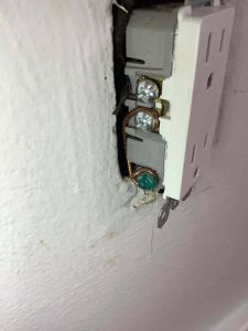 close up of a white outlet with a bootleg ground wire